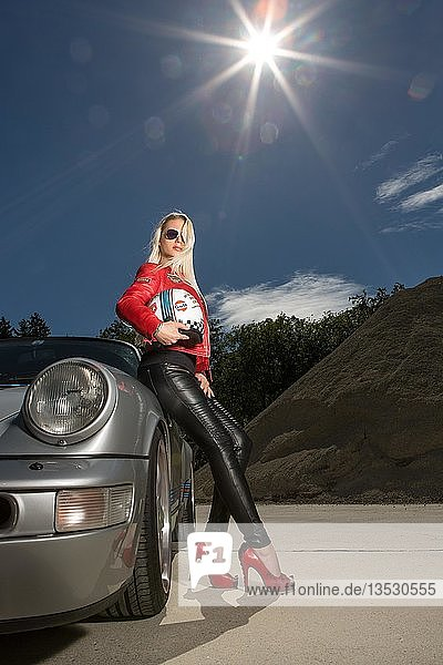 Young woman with long blonde hair poses with Porsche 911 Carrera 4