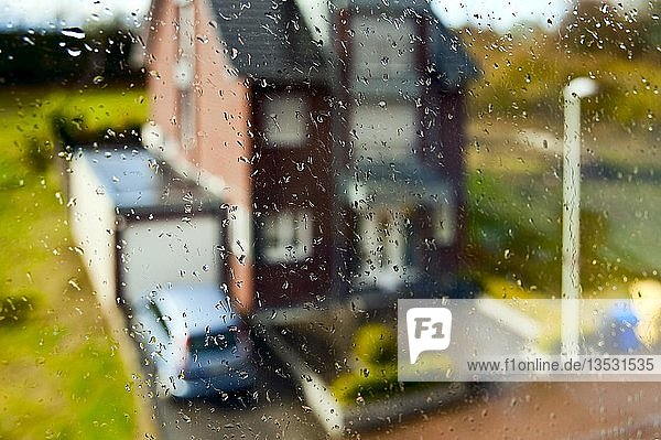 Blick durch ein verregnetes Fenster auf das Nachbarhaus