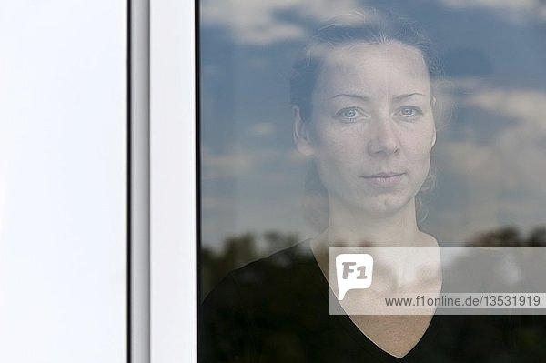 Junge Frau hinter einer Fensterscheibe  Porträt
