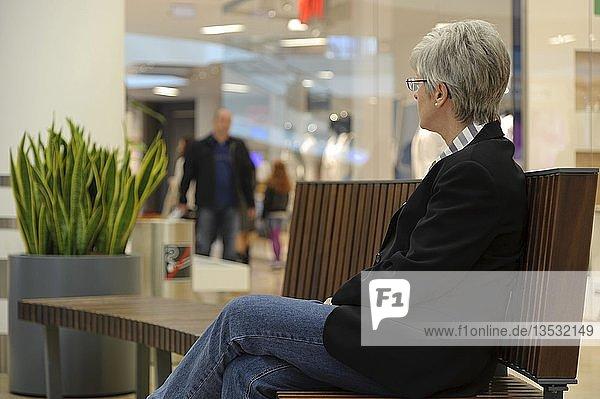 Frau sitzt auf einer Bank und beobachtet einen Mann