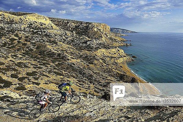 Zwei Mountainbiker radeln an Felsküste  Red Beach  Matala  Kreta  Griechenland  Europa