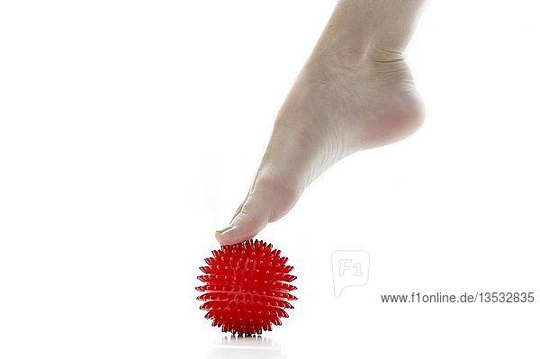 Fuß steht mit Zehenspitzen auf einem roten Massageigel