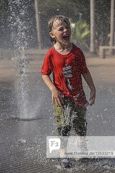 Boy stands in a fountain and gets sprayed  Puerto Iguazu  Argentina  South America