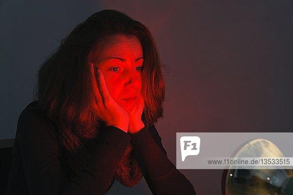 Junge Frau im Licht einer Rotlichtlampe