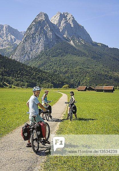 Three cyclists on bike tour are on bike path  in the back Zugspitze  Tegernauweg  near Grainau  crossing the Alps  Garmisch-Partenkirchen  Upper Bavaria  Bavaria  Germany  Europe