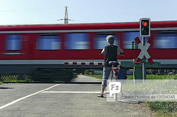 Frau wartet mit Fahrrad vor einem Bahnübergang