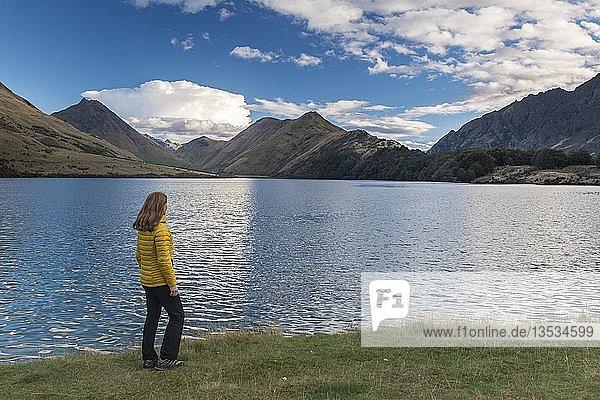 Wanderin steht am Ufer des Moke Lake bei Queenstown  See mit Bergen  Otago  Südinsel  Neuseeland  Ozeanien
