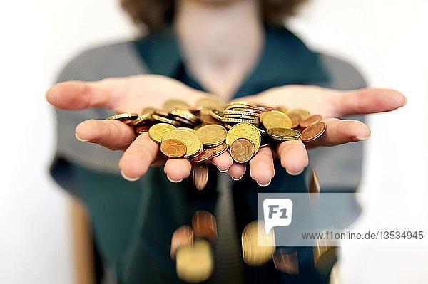 Hände lassen Geld durch die Finger gleiten