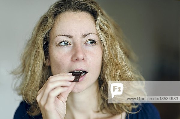 Junge Frau isst genussvoll Schokolade