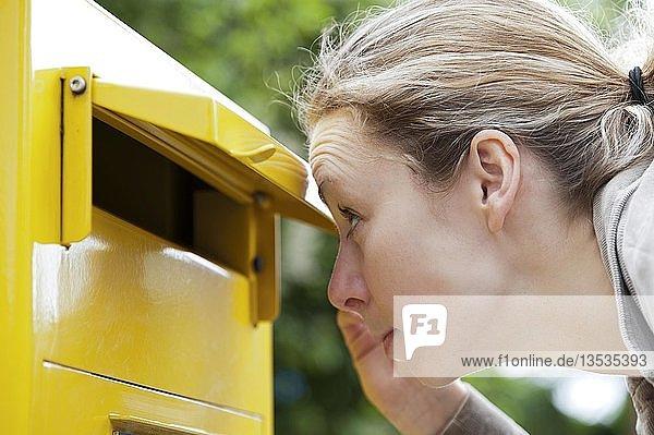 Junge Frau schaut neugierig in einen Briefkasten