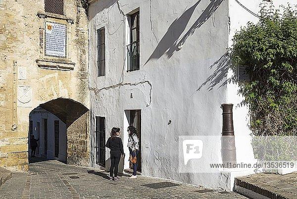 Zwei junge Frauen  die am Segur-Tor in Vejer de la Frontera  Cadiz-Provinz  Andalusien  Spanien plaudern