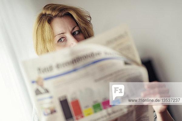 Junge Frau liest eine Zeitung mit Prognosen zur Bundestagswahl  Deutschland  Europa