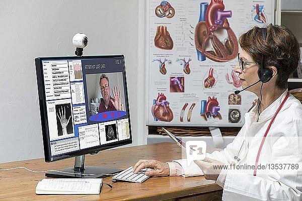Symbolfoto zur Telemedizin  Ärztin in einer Praxis  kommuniziert mit dem Patienten über eine Webcam  Patientendaten und Befunde auf dem Monitor  Deutschland  Europa
