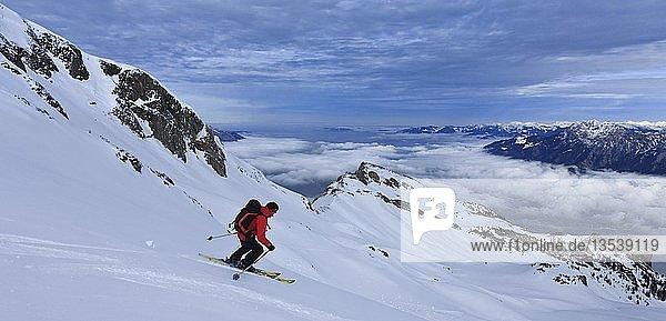Skitour  Skifahrer bei der Abfahrt vom Alvier  Nebel über dem Rheintal  Alviergruppe  Appenzeller Alpen  Kanton St. Gallen  Schweiz  Europa
