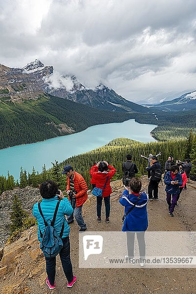 Asian tourists pose for a photo  turquoise lake  Peyto Lake  Rocky Mountains  Banff National Park  Alberta Province  Canada  North America