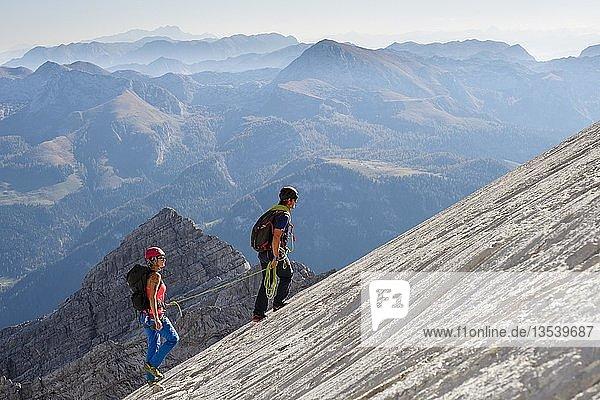 Bergführer führt eine junge Frau am kurzen Seil durch eine Felswand  Wiederroute  Watzmann  Schönau am Königsee  Berchtesgadener Land  Bayern  Deutschland  Europa