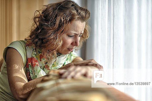 Junge Frau mit traurigem Gesichtsausdruck  auf Sofa