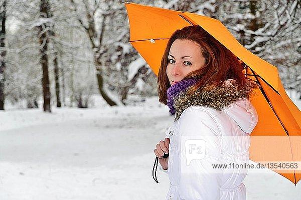 Junge Frau mit gelbem Schirm im Winterwald