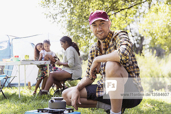 Portrait confident man heating teapot on camping stove at sunny campsite