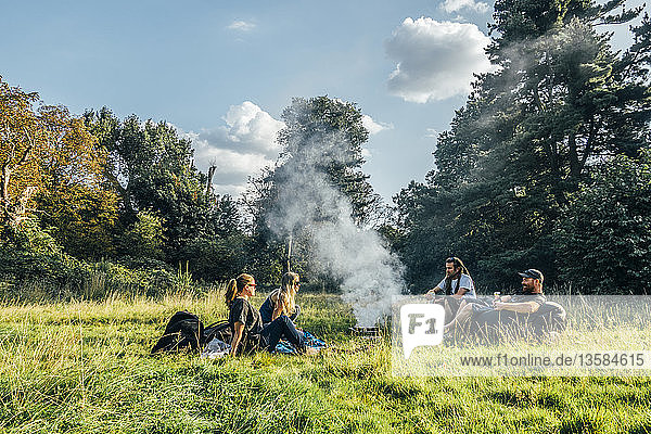 Friends camping  relaxing around campfire in remote field