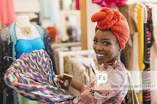 Portrait smiling  confident young woman in headscarf shopping in clothing store