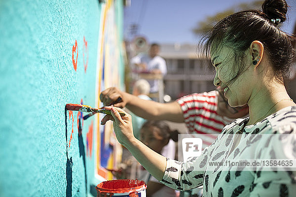 Smiling female volunteer painting mural on sunny wall