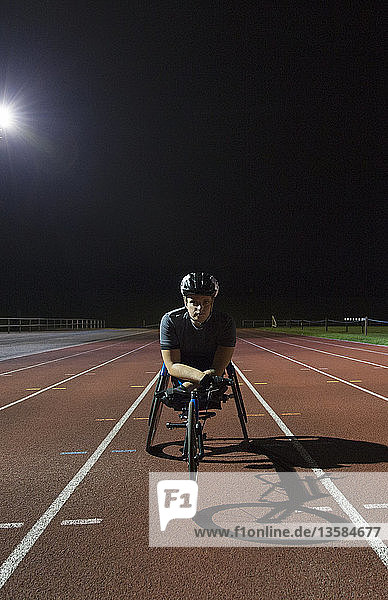 Portrait confident paraplegic athlete on sports track training for wheelchair race at night