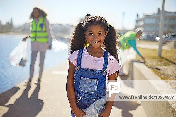 Portrait smiling girl volunteer cleaning up litter on sunny boardwalk