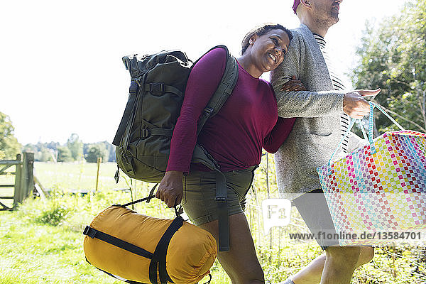 Affectionate couple carrying camping equipment