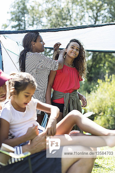Mother fixing daughters hair at campsite