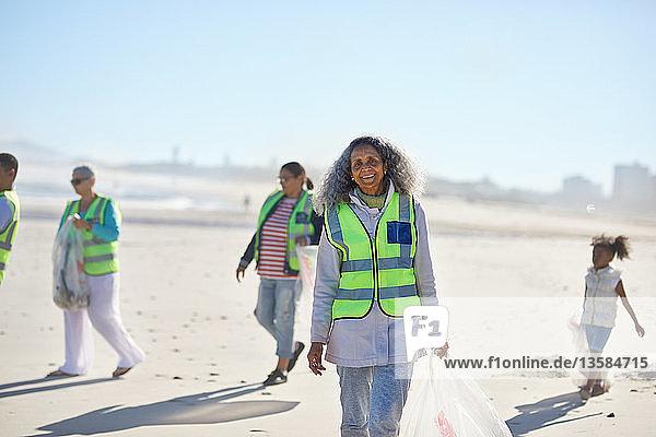 Portrait confident senior woman volunteer cleaning up litter on sunny beach