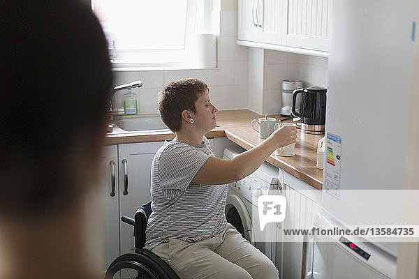 Young woman in wheelchair preparing tea in apartment kitchen