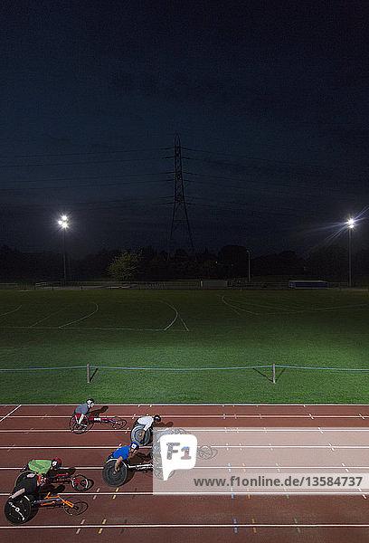 Paraplegic athletes speeding along sports track in wheelchair race at night Paraplegic athletes speeding along sports track in wheelchair race at night