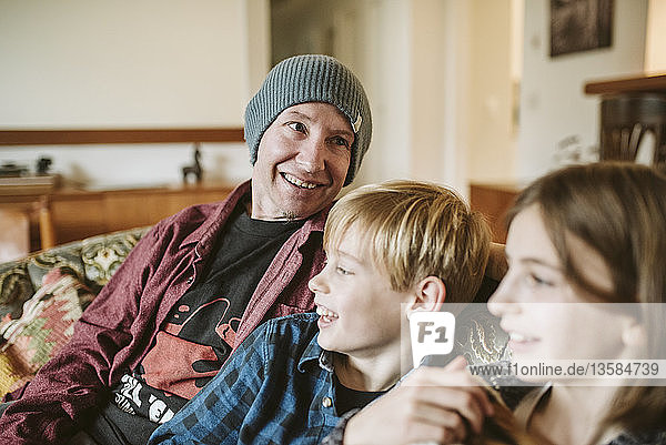 Father and children relaxing on living room sofa