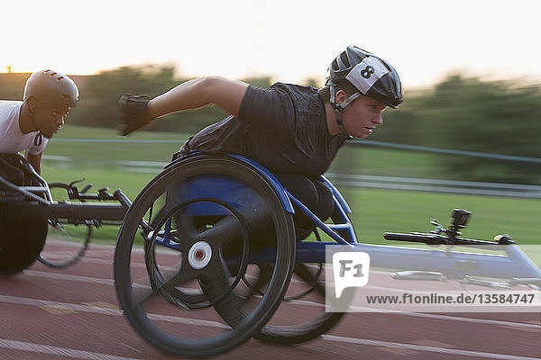 Determined young female paraplegic athlete speeding along sports track in wheelchair race