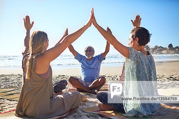 Group joining hands in circle on sunny beach during yoga retreat