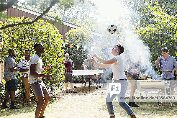Male friends playing soccer and ping pong  enjoying backyard barbecue