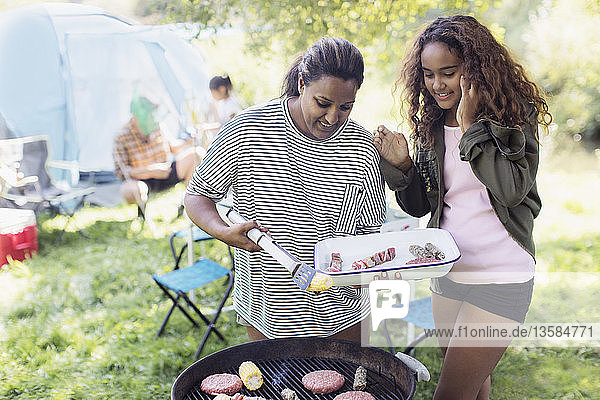 Mother and daughter barbecuing at campsite
