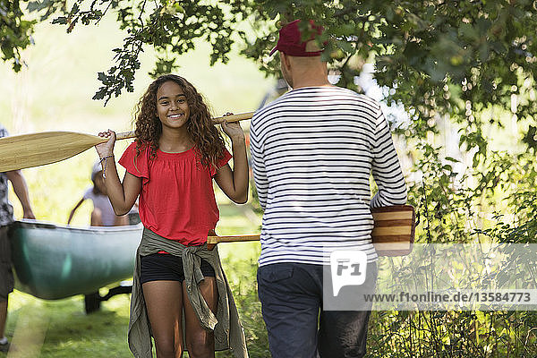 Father and daughter carrying canoe oars