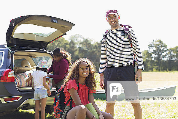 Portrait happy father and daughter camping  unloading car