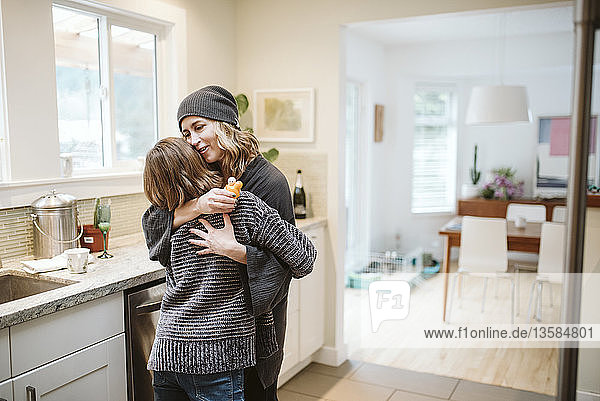 Affectionate mother and daughter hugging in kitchen