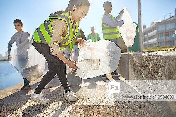 Woman volunteer picking up plastic litter on sunny boardwalk