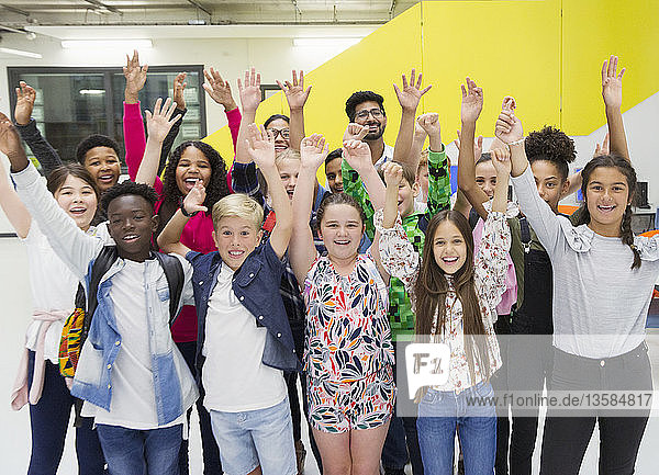Portrait enthusiastic junior high students and teachers cheering with arms raised
