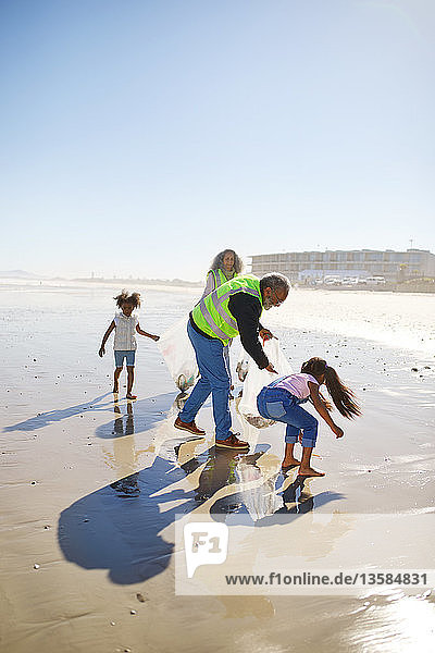 Volunteers cleaning up litter on sunny wet sand beach