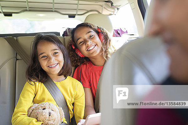 Happy sisters riding in back seat of car
