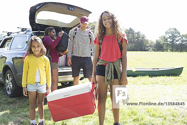 Portrait happy family camping  unloading car