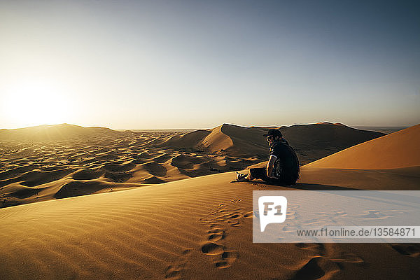 Male traveler enjoying sunny sandy desert view  Sahara  Morocco
