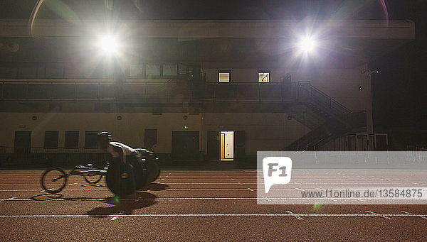 Male paraplegic athlete training for wheelchair race on sports track at night