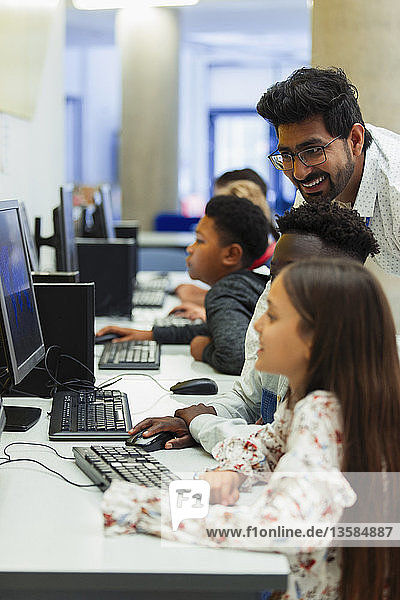 Teacher helping junior high students using computer in computer lab