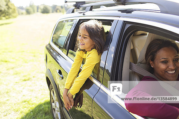 Carefree girl leaning out window of car